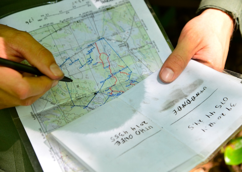 Senior Airman Leo Avila, 709th Airlift Squadron C-5M Super Galaxy engineer, uses coordinates to mark his crew's position on a map during a combat survival training exercise July 16, 2015, at the Blackbird State Forest near Smyrna, Del. The crew was equipped with a compass and a map to navigate several miles of woodland and marshy terrain during the exercise. (U.S. Air Force photo/Airman 1st Class William Johnson)