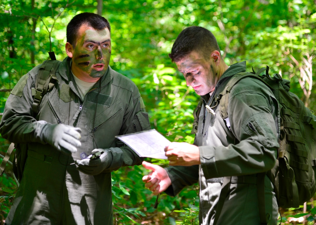 Senior Airman Leo Avila, 709th Airlift Squadron C-5M Super Galaxy engineer, left, and Senior Airman Dan Bates, 9th AS C-5M loadmaster, right, use a compass and a map to navigate to a checkpoint during a combat survival training exercise July 16, 2015, at the Blackbird State Forest near Smyrna, Del. Avila and Bates navigated with three other members of their team through several miles of forest to be rescued by friendly forces after escaping from enemy combatants. (U.S. Air Force photo/Airman 1st Class William Johnson)