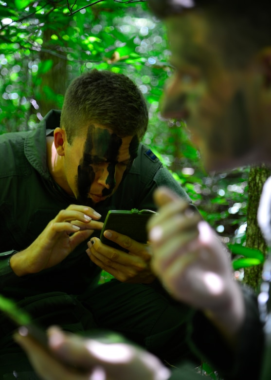 Capt. Rob Willoughby, 9th Airlift Squadron C-5M Super Galaxy pilot, applies camouflage paint to his face during a combat survival training exercise July 16, 2015, at the Blackbird State Forest near Smyrna, Del. Willoughby was part of a five-man team that was evading enemy forces after being captured in the exercise. (U.S. Air Force photo/Airman 1st Class William Johnson)
