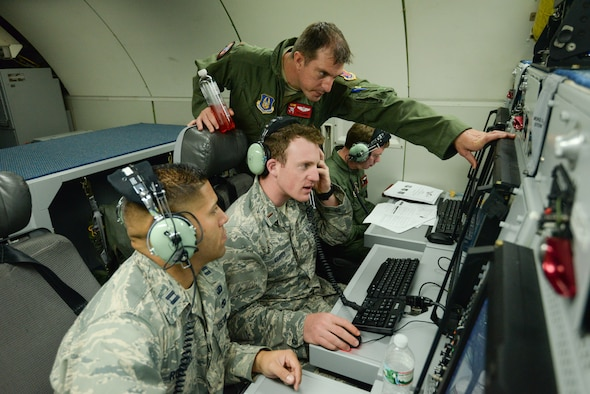 Maj. Phil Schredl, an air weapons officer assigned to the 513th Operations Support Squadron, shows upgraded software on board an E-3G Sentry Block 40/45 to 2nd Lt. Ryan Kramer and Capt. Jeff Rodriguez, both E-3 program managers, July 18 during a training mission. The 513th Air Control Group invited eight program managers on board to see the product of their work and to discuss future improvements to the Airborne Warning and Control System aircraft. (U.S. Air Force photo by Staff Sgt. Caleb Wanzer)