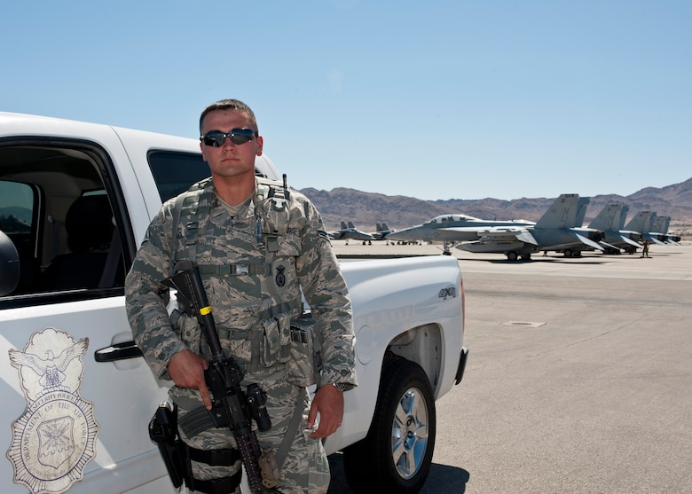 Airman 1st Class Michael Cordova, 99th Security Forces Squadron member, stands guard on the flightline during Red Flag 15-3 on Nellis Air Force Base, Nev., July 17, 2015. While on duty, Cordova provides security, armed response to any priority-level resource in his assigned area of operation, and ensures only authorized personnel are on the flightline. During Red Flag exercises, Cordova's assigned area of operation includes over 100 aircraft. (U.S. Air Force photo by Airman 1st Class Jake Carter)