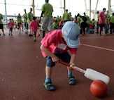 A child lines up his next shot in one of the games played during the St. Martin's Special Children's Day event July 22, 2015 at Spangdahlem Air Base, Germany. The event offers special needs children from local schools a chance to interact with the Saber Community. (US Air Force photo by Senior Airman Sarah Denewellis/Released)