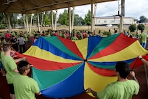Volunteers from the Spangdahlem community play alongside children from a local school as part of St. Martin's Special Children's Day event July 22, 2015 at Spangdahlem Air Base, Germany. The event originated at Spangdahlem in 1992. (US Air Force photo by Senior Airman Sarah Denewellis/Released)