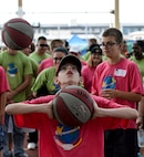 A child from St Martin's School in Bitburg, Germany, takes part in a round of basketball during the St. Martin's Special Children's Day event July 22, 2015 at Spangdahlem Air Base, Germany. The base community hosted the annual event to offer a day of fun and games for special needs youth. (US Air Force photo by Senior Airman Sarah Denewellis/Released)
