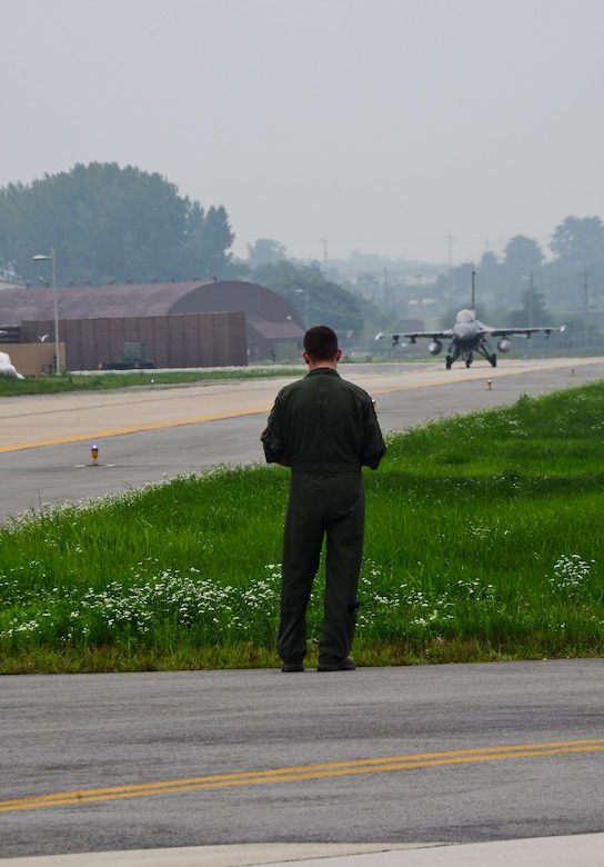 """Capt. Ely Smith, 36th Fighter Squadron scheduling officer and flight lead, watches as an F-16C """"Fighting Falcon"""" prepares to take-off on Osan Air Base, South Korea, July 22, 2015. In the past year, the squadron has flown more than 4,500 sorties, giving the 36th the largest F-16 flying program in the Combat Air Force. (U.S. Air Force photo/Senior Airman Kristin High)"""
