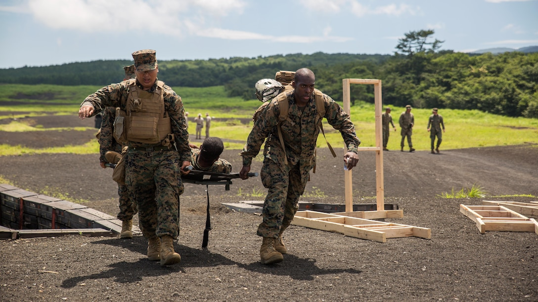 Hospital Corpsman Mc Joe Evans Bautista, left, and Hospital Corpsman 3rd Class Trevor A. Tisby, right, stationed with Combat Logistics Company 36 aboard Marine Corps Air Station Iwakuni, Japan, carry Sgt. Kendrick Moore, a motor transport operator with CLC-36, to a safety vehicle during Exercise Dragon Fire 2015 at Combined Arms Training Center Camp Fuji, Japan, July 20, 2015. Dragon Fire enables Marines and Sailors to engage their combat mindset to prepare for the mental and physical stresses of a combat zone. Moore simulated an unexpected injury during this training scenario that allowed the corpsmen to respond as if there was a real emergency.