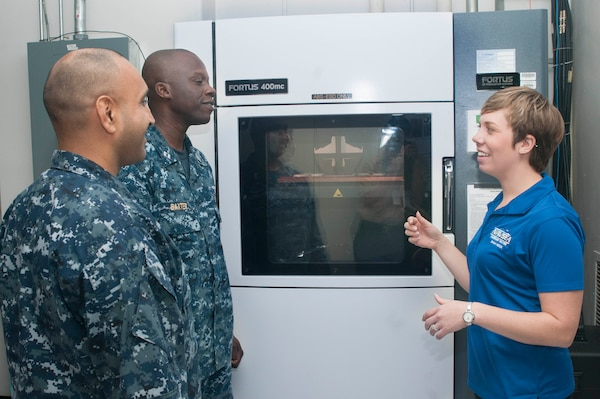 Carolyn Lambeth, a mechanical engineer at Combat Direction Systems Activity, right, explains the process on addictive manufacturing and 3D printing to Sailors during the U.S. Navy's first Maker Faire titled Print the Fleet. The event showcased additive manufacturing techniques for Sailors and other stakeholders attending the two-day event. (U.S. Navy photo by Mass Communication Specialist Seaman Jonathan B. Trejo/ Released)