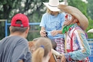 Jason Dent, also known as Whistle-Nut the rodeo clown, grins as he helps child after child get on the bull, Ole.