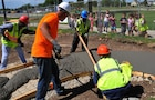 Children from the Forsyth Child Development Center look on as construction workers pour cement for a raceway at the preschool's playground, July 14.
