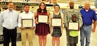 (From left) Peter Howell, Fort Riley Commissary Director, Daniel Rivera, 17, from Junc¬tion City, Katherine Dixon, 17, from Manhattan, and Caitlyn Hartung, 17, from Junction City, Sgt. 1st Class Samuel Cook, 1st Infantry Division Artillery Brigade, Hold Up Bat¬tery, 1st Infantry Division, and his son Samad, 7 years old, and Brian Roucky, former Fort Riley Commissary Director, pose with plaques for the recipients of the Scholarships for Military Children during a ceremony at the Commissary, July 15, at Fort Riley. Four high school students and one college student from the local area received a $2,000 check made payable to the college or university selected by the scholarship recipient. (Not pictured, Samara Cook and Megan Ochoa).