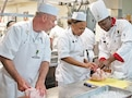 Sgt. 1st Class John Evers (left) observes as Staff Sgt. Jeffrey Matthews (right), DHHB, 1st Inf. Div., demon¬strates a technique for preparing a whole chicken to Pvt. Tyshala Joyner July 15 at the Fort Riley Food Service Lab. Evers and Joyner were among six Army Reserve Soldiers from the 1006th QM Co., 143rd Expeditionary Sust. Command, who learned from Matthews and other 1st Inf. Div. Soldier chefs during a two-week refresher course.