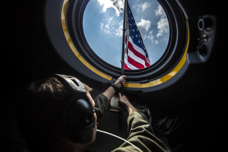 Capt. Brian Schmidt, 1st Special Operations Group Detachment 2 pilot, raises a flag out of the first AC-130J Ghostrider on Hurlburt Field, Fla., July 29, 2015. The 1st Special Operations Wing received Air Force Special Operations Command's first AC-130J that will be flown by the 1st SOG Det. 2 and maintained by the 1st Special Operations Aircraft Maintenance Squadron. (U.S. Air Force photo/Senior Airman Christopher Callaway)