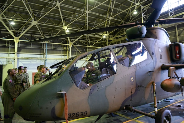 Aircrew members with the 459th Airlift Squadron take seats in an OH-1 Omega helicopter at Tachikawa Air Base, Japan, July 16, 2015. The OH-1, which was part of a static display hosted by Japan Ground Self-Defense Force, is the first helicopter designed and manufactured in Japan. (U.S. Air Force photo by Airman 1st Class Elizabeth Baker/Released)