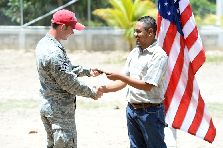 Gabriela Mistral School Principal Abraham Ruiz hands a gift to U.S. Air Force Staff Sgt. Nathan Rosier, 823rd Expeditionary RED HORSE Squadron structural craftsman and Tampa, Fla., native, as a token of his appreciation for the work that he and other members of the New Horizons Honduras 2015 training exercise performed in the construction of a new two-classroom schoolhouse during a ribbon-cutting ceremony at Ocotes Alto, Honduras, July 28, 2015. Ruiz gave a gift to every member of the New Horizons team that worked in the construction of the building. New Horizons was launched in the 1980s and is an annual joint humanitarian assistance exercise that U.S. Southern Command conducts with a partner nation in Central America, South America or the Caribbean. The exercise improves joint training readiness of U.S. and partner nation civil engineers, medical professionals and support personnel through humanitarian assistance activities. (U.S. Air Force photo by Capt. David J. Murphy/Released)