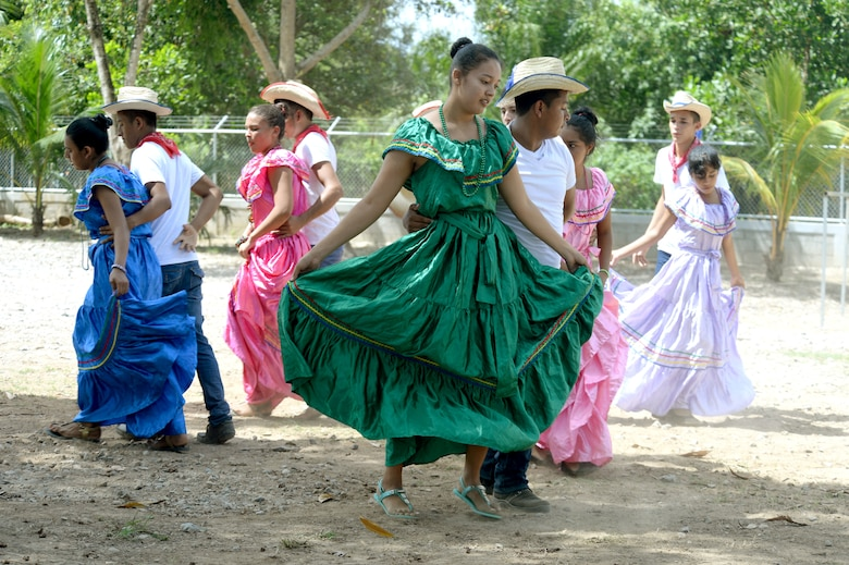 Gabriela Mistral students perform a traditional dance during the ribbon-cutting ceremony at the Gabriela Mistral school in Ocotes Alto, Honduras, July 28, 2015. The ribbon-cutting ceremony celebrated the opening of the new two-classroom schoolhouse. The schoolhouse was one of the key projects that occurred as part of the New Horizons Honduras 2015 training exercise taking place in and around Trujillo, Honduras. New Horizons was launched in the 1980s and is an annual joint humanitarian assistance exercise that U.S. Southern Command conducts with a partner nation in Central America, South America or the Caribbean. The exercise improves joint training readiness of U.S. and partner nation civil engineers, medical professionals and support personnel through humanitarian assistance activities. (U.S. Air Force photo by Capt. David J. Murphy/Released)