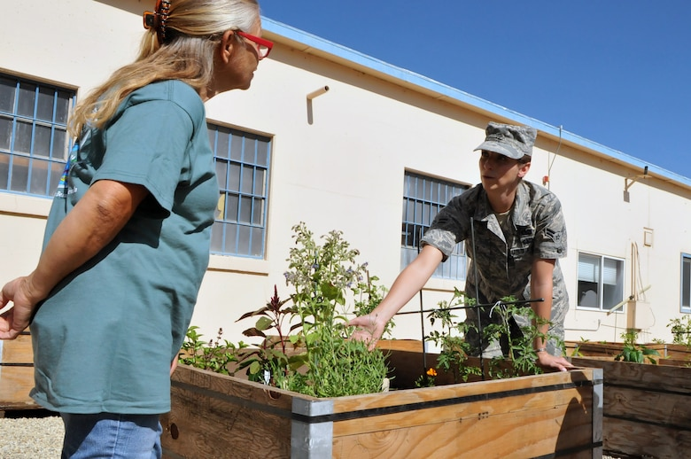 Airman 1st Class Kristine Wiley, right, works on the Nevada Air National Guard Base community garden with University of Nevada, Reno Cooperative Extension Master Gardener Pamela Van Hoozer on July 8, 2015. Wiley, with approval from base leadership, started work this summer on creating a community garden that now houses 10 raised and three ground plant beds just west of the base firehouse. Photo by Nevada Air Guard Tech Sgt. Emerson Marcus.
