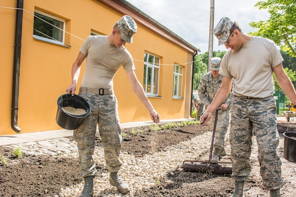 U.S. Air Force Senior Airman Nathaniel Kiger and Staff Sgt. Conrad Marine, both with the 139th Civil Engineer Squadron, Missouri Air National Guard, spread grass seed during the reconstruction of the Naujenu Orphanage near Daugavpils, Latvia, July 20, 2015.  The 139th CE was participating in the Humanitarian Civic Assistance project through the United States European Command, that pairs units training requirements with humanitarian needs.   (U.S. Air National Guard photo by Senior Airman Patrick P. Evenson/Released)