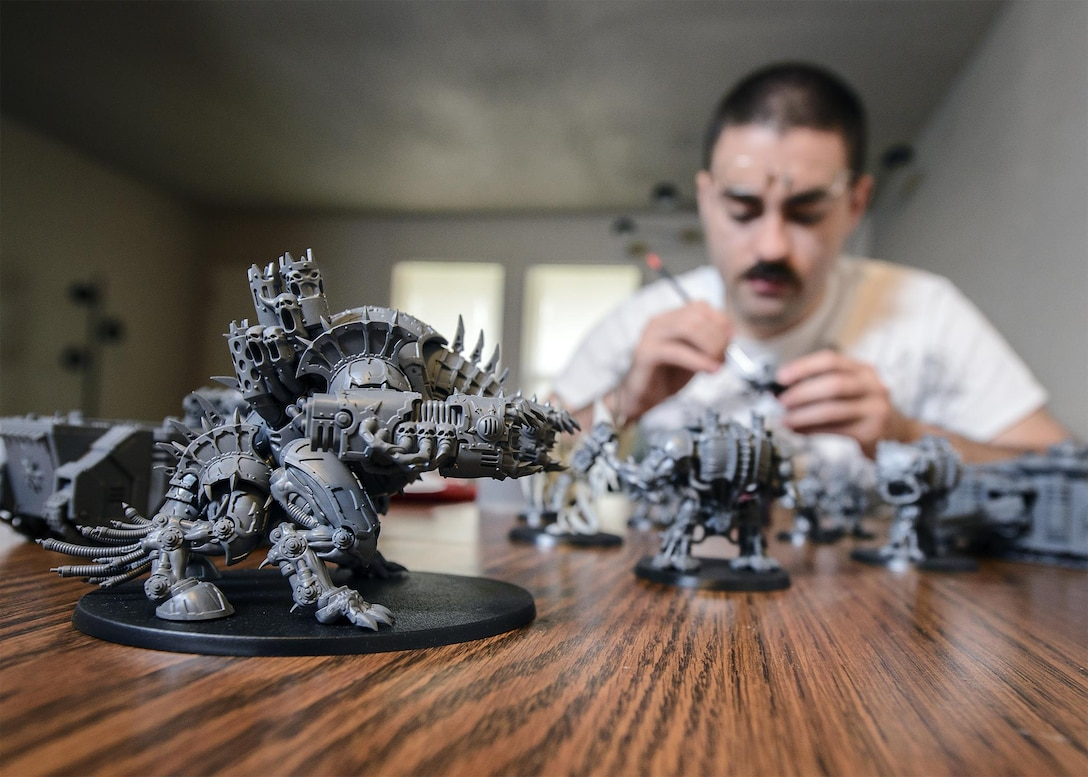 Senior Airman Thomas White, a 71st Operations Support Squadron Airman, enjoys some downtime as he customizes Warhammer 40,000 units at his home in Enid, Oklahoma, June 16. (U.S. Air Force photo by David Poe)