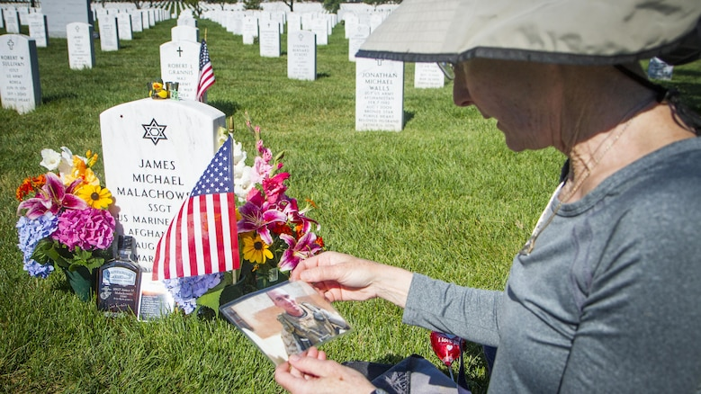 """Alison Malachowski holds a photograph of her son, U.S. Marine Corps Staff Sgt. James Malachowski, in front of his grave in Section 60 of Arlington National Cemetery, July 22, 2015. Staff Sgt. Malachowski, who was with the 2nd Battalion of the 8th Marines, was killed by an improvised explosive device during his fourth combat depoloyment on March 20, 2011, while his unit was raising the Afghanistan national flag over a small compound near Patrol Base Dakota in Marjah Province. """"He died a terrible, painful death,"""" said Alison. """"But he did not scream or cry and I know why - it was so he wouldn't frighten his guys."""" (U.S. Army photo by Sgt. Ken Scar)"""