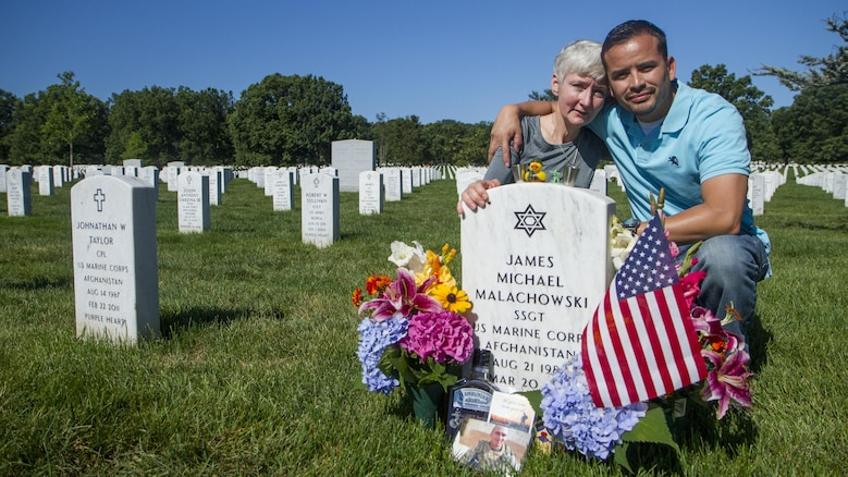 Alison Malachowski and former Marine Sgt. Danny Gonzalez hold each other at the grave marker of U.S. Marine Corps Staff Sgt. James Malachowski - Alison's son and Gonzalez's best friend and fellow Marine - in Section 60 of Arlington National Cemetery, July 22, 2015. The two have remained close since James was killed by an improvised explosive device while on his fourth combat deployment in Afghanistan in 2011. Staff Sgt. Malachowski - who was by all accounts a superior Marine on the fast track to the upper-echelons of military service - was with the 2nd Battalion of the 8th Marines when he was killed on March 20, 2011, while his unit was raising the Afghanistan national flag over a small compound near Patrol Base Dakota in Marjah Province. (U.S. Army photo by Sgt. Ken Scar)