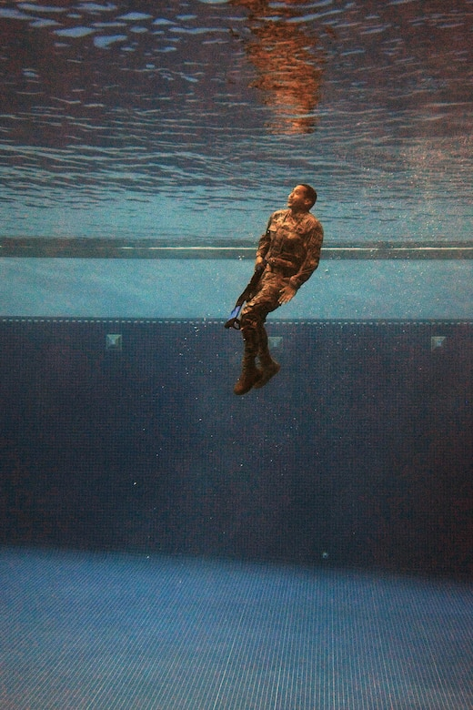 A security forces Airman plunges into the combat water survival test at the U.S. Air Force Academy, Colo., July 17, 2015. The event was part of a daylong course for Airmen across the Front Range area to determine if they are physically and mentally ready to attend the U.S. Army Pre-Ranger Training Assessment Course, a prerequisite to attending U.S. Army Ranger School at Fort Benning, Ga. (U.S. Air Force photo/Jason Gutierrez)