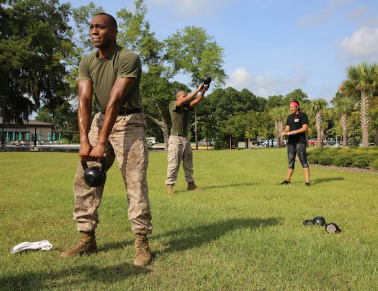 Staff Sgt. Vincent Huggan and Sgt. Osias Lozano perform kettle bells swings during the Tactical Athlete Challenge aboard Marine Corps Air Station Beaufort July 29. Every event in the challenge was based on exercises in the High Intensity Tactical Training program. Huggan is a training chief with Marine Aviation Logistics Squadron 31. Lozano is a training non-commissioned officer with MALS-31.