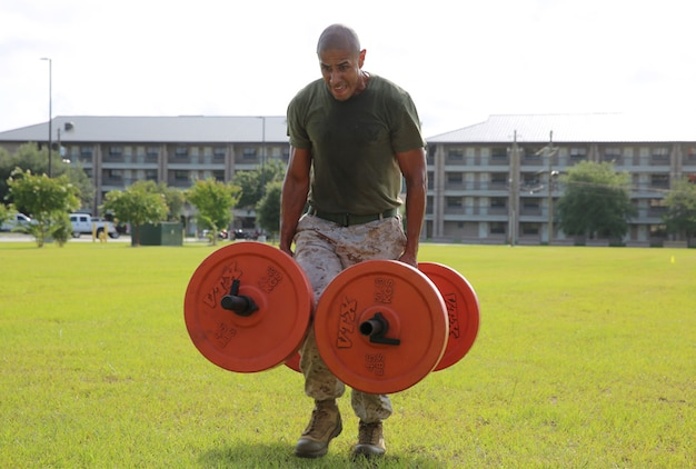 Sgt. Osias Lozano carries weights during the Tactical Athlete Challenge held aboard Marine Corps Air Station Beaufort July 29. The 400 yard tactical course includes tire flips, sprints, and fireman carries. Lozano is a training non-commissioned officer with Marine Aviation Logistics Squadron 31.