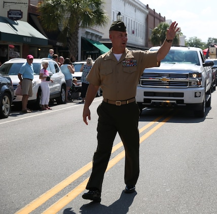 Col. Peter D. Buck waves at spectators during the 60th Annual Beaufort Water Festival Parade through downtown Beaufort July 25. The Festival is a ten-day celebration showcasing Lowcountry cuisine, arts and crafts, and more than two-dozen individual sporting, water, and music events. Buck is the commanding officer of Marine Corps Air Station Beaufort.