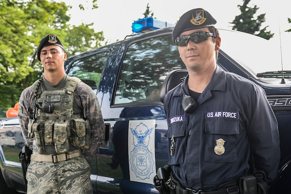 U.S. Air Force Airman 1st Class Logan Thimm, 374th Security Forces Squadron patrolman, and Masafumi Shinozuka, civilian guard, pose in front of a patrol truck at Yokota Air Base, Japan, July 29, 2015. Civilian guards have protected Yokota's mission by securing the gates for years, but now they have begun augmenting for security forces personnel on patrol. (U.S. Air Force photo by Airman 1st Class Elizabeth Baker/Released)