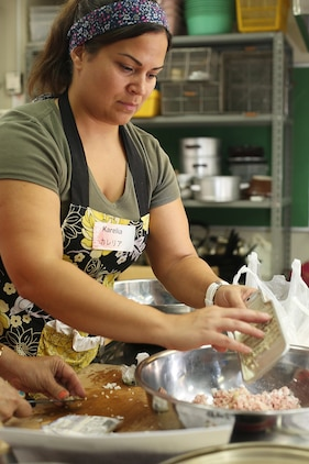 Karelia Graham, a resident of Marine Corps Air Station Iwakuni mixes diced garlic and ground pork to make Shumai during a Japanese cooking class at Fukushi Kaikan in Iwakuni, July 24, 2015. The station's cultural adaptation program coordinates the class three times a year, and it is one of many ways to indulge in local cuisine. Participants learned how to make Oriental dishes such as Chinese pork dumpling, seaweed soup and fried rice.