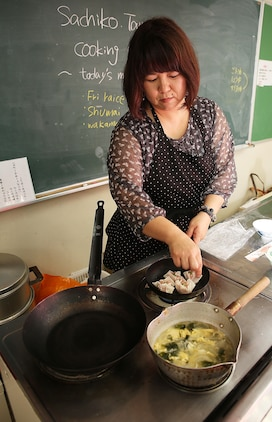 Sachiko Tamura, a member of Eating Habits Improvement Promotion, cooks Shumai and Wakame soup during a Japanese Cooking Class at Fukushi Kaikan in Iwakuni City, Japan, July 24, 2015. Tamura acted as the culinary chef for Marine Corps Air Station Iwakuni residents participating in the class. Coordinated by the Cultural Adaption Program aboard station, residents also prepared traditional fried rice, which is an essential part of Japanese meals.