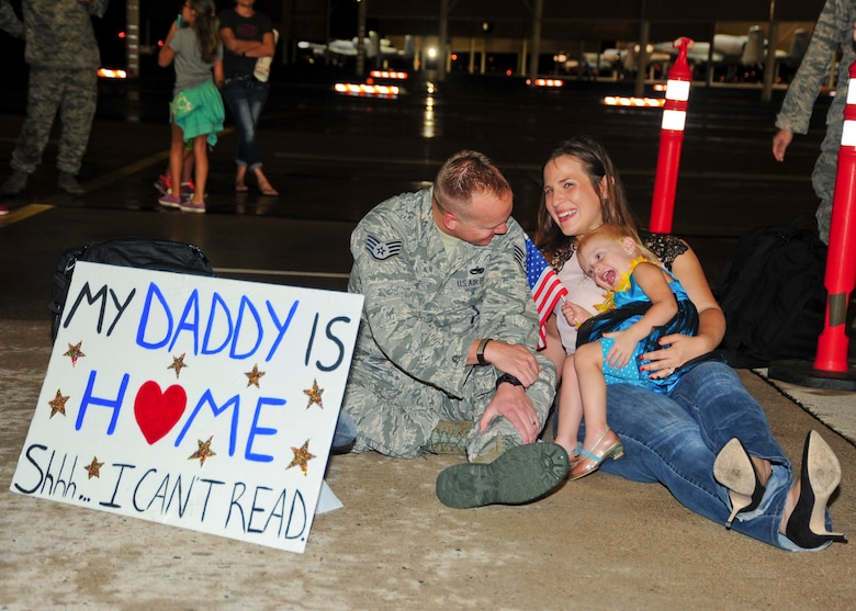 U.S. Air Force Staff Sgt. Bryan Kessler, 355th Maintenance Group A-10 Thunderbolt II quality assurance inspector, shares a moment with his wife, Danielle, and daughter, Lilah, at Davis-Monthan Air Force Base, Ariz., after returning home from a 6-month deployment July 29, 2015. Kessler deployed as part of the first European Theater Security Package in support of Operation Atlantic Resolve.  (U.S. Air Force photo by Senior Airman Chris Massey/Released)