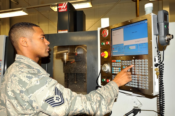 Tech. Sgt. Joshua Briscoe, 69th Maintenance Squadron metals technology craftsman, operates a Computer Numerical Control (CNC) machine, which cuts shapes out of sheets of metal. Briscoe was named Warrior of the Week for the fifth week of July, 2015. (U.S. Air Force photo/Staff Sgt. Susan L. Davis)