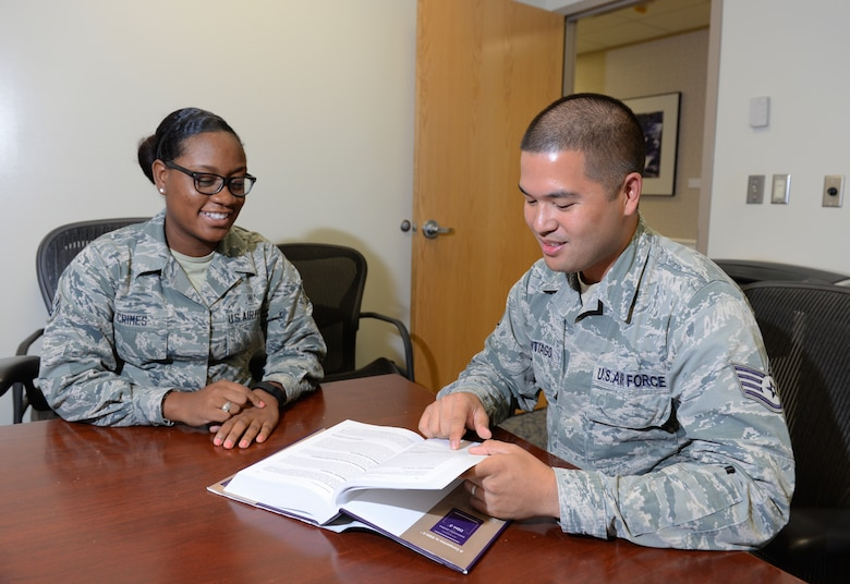 Airman 1st Class Chelsea Crimes, 36th Medical Operations Squadron mental health administrator, left, and Staff Sgt. Carlo Santiago, 36th MDOS mental health NCO in charge and Alcohol and Drug Abuse Prevention and Treatment program technician, review definitions of medical diagnoses July 17, 2015, at Andersen Air Force Base, Guam. The 36th Medical Group Mental Health Clinic team stands ready to assist Airmen by providing a variety of mental health services. (U.S. Air Force photo by Senior Airman Alexander W. Riedel/Released)