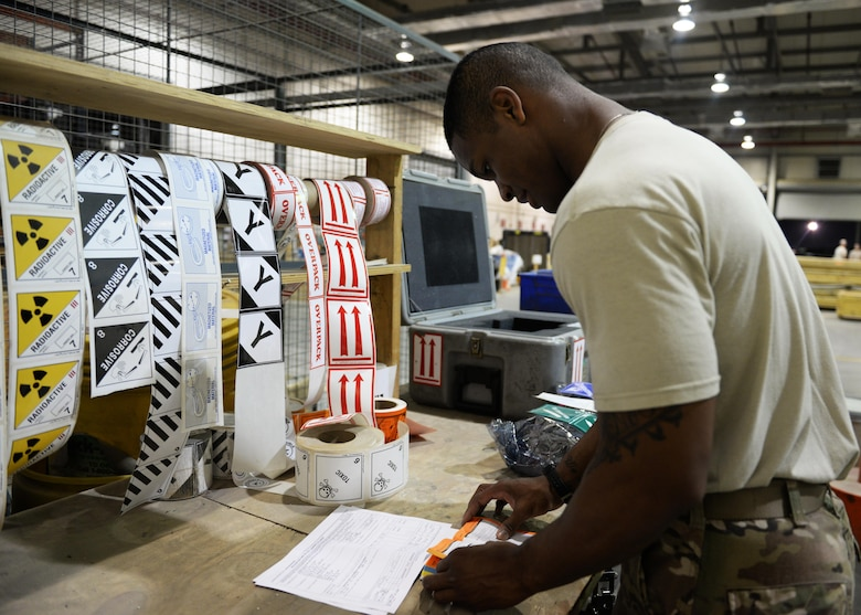 U.S. Air Force Senior Airman Kionne Lewis, 455th Expeditionary Logistics Readiness Squadron's Traffic Management Office cargo movement specialist, prepares to label material to be shipped out to Al Udied, Air Base, Qatar, July 21, 2015, at Bagram Airfield, Afghanistan. Lewis and his team are responsible for ensuring all shipments from the AOR, to include hazardous and classified materials as well as aircraft parts, are ready for transport. (U.S. Air Force photo by Senior Airman Cierra Presentado/Released)