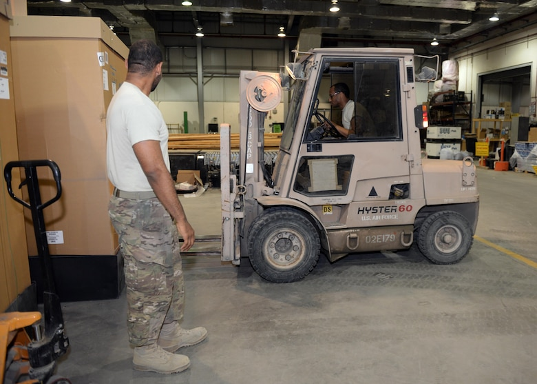 U.S. Airmen from the 455th Expeditionary Logistics Readiness Squadron Traffic Management Office bring in new material July 21, 2015, at Bagram Airfield, Afghanistan. The team is responsible for ensuring all shipments from the AOR to include hazardous and classified materials as well as aircraft parts are ready for transport. (U.S. Air Force photo by Senior Airman Cierra Presentado/Released)