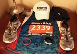 """A tradition for runners to ensure they have everything they need for the day of their race, is to set out their gear the night before. The wrist bands help motivate during a run. """"For Boston"""" bands like the one in the middle were sold to raise funds for the victims of the 2013 bombing. The """"INSPIRE"""" band is a gift from his friend Maria who is among those who inspired him to run the Boston Marathon and the purple band has the word """"Hope"""" inscribed on it. Chamberlain wore the purple band at the request of his brother's wife, Irene, for his brother and coworkers whose spouses were battling cancer."""