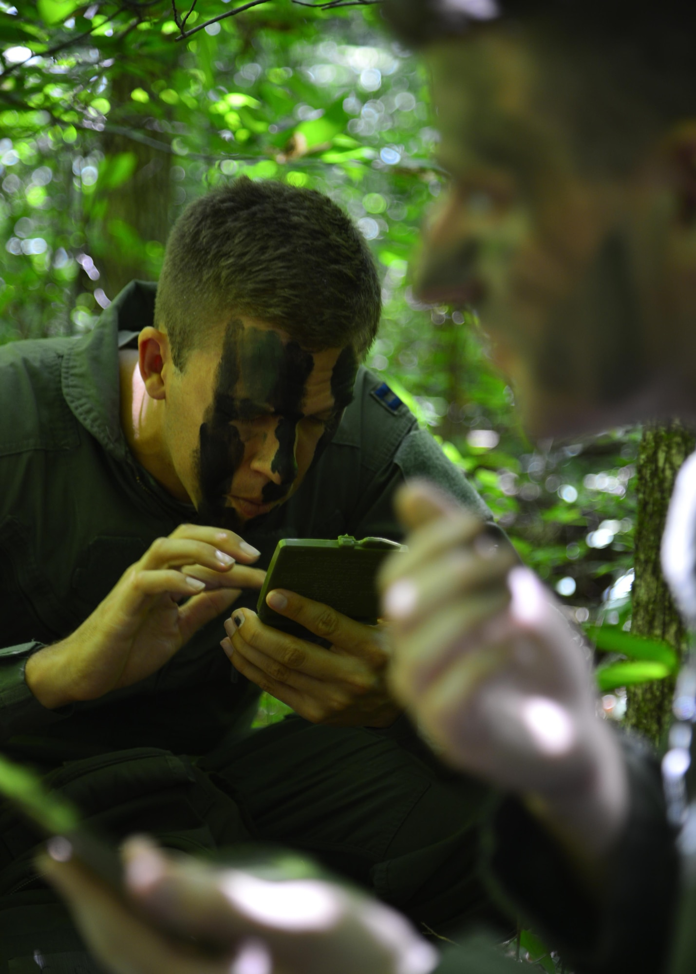 Capt. Rob Willoughby, a C-5M Super Galaxy pilot assigned to the 9th Airlift Squadron, applies camouflage paint to his face during a combat survival training exercise July 16, 2015, at the Blackbird State Forest near Smyrna, Del. Willoughby was part of a five-man team that was evading enemy forces after being captured in the exercise. (U.S. Air Force photo/Airman 1st Class William Johnson)