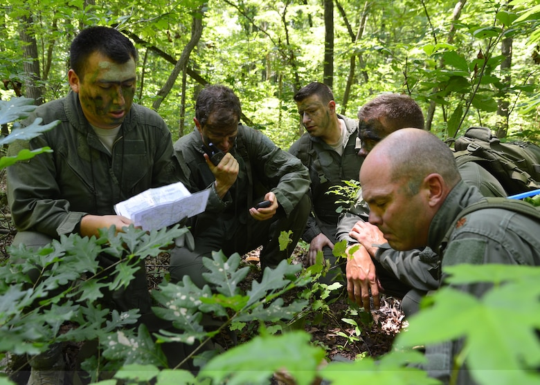 Members of the 709th and 9th Airlift Squadrons use a map to radio in their location to friendly rescue personnel during a combat survival training exercise July 16, 2015, at the Blackbird State Forest near Smyrna, Del. The aircrew evaded enemy forces for several miles before rendezvousing with friendly rescue forces. (U.S. Air Force photo/Airman 1st Class William Johnson)