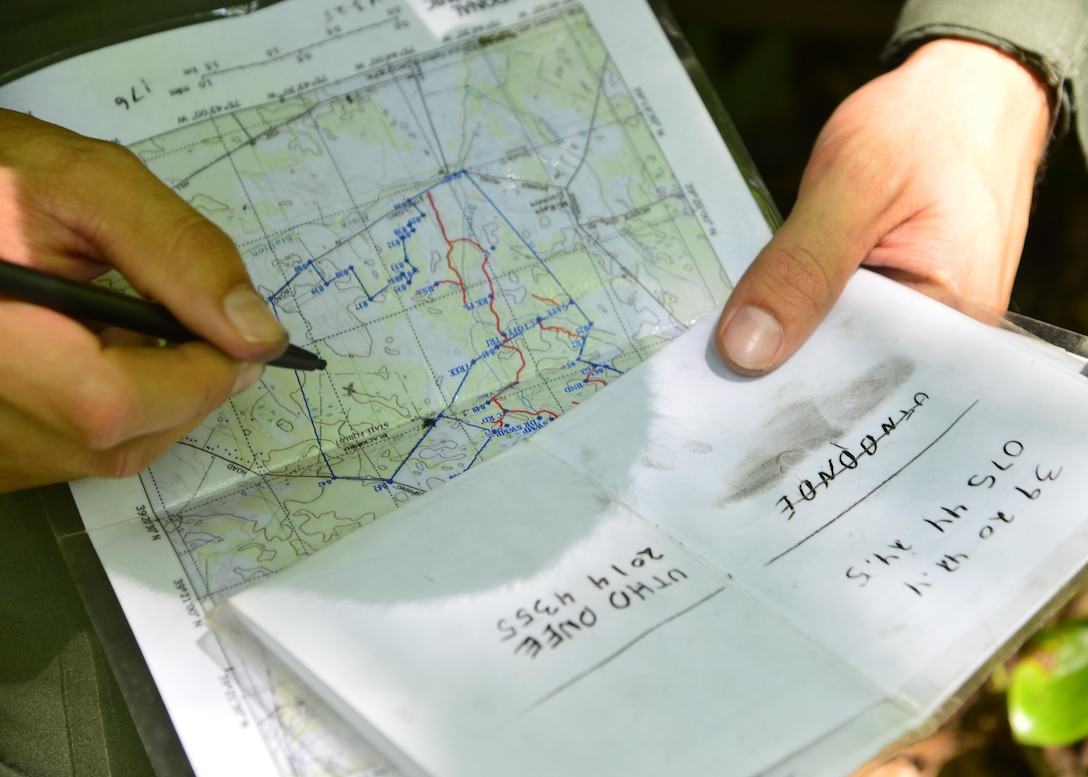 Senior Airman Leo Avila, a C-5M Super Galaxy engineer assigned to the 709th Airlift Squadron, uses coordinates to mark his crew's position on a map during a combat survival training exercise July 16, 2015, at the Blackbird State Forest near Smyrna, Del. The crew was equipped with a compass and a map to navigate several miles of woodland and marsh terrain during the exercise. (U.S. Air Force photo/Airman 1st Class William Johnson)