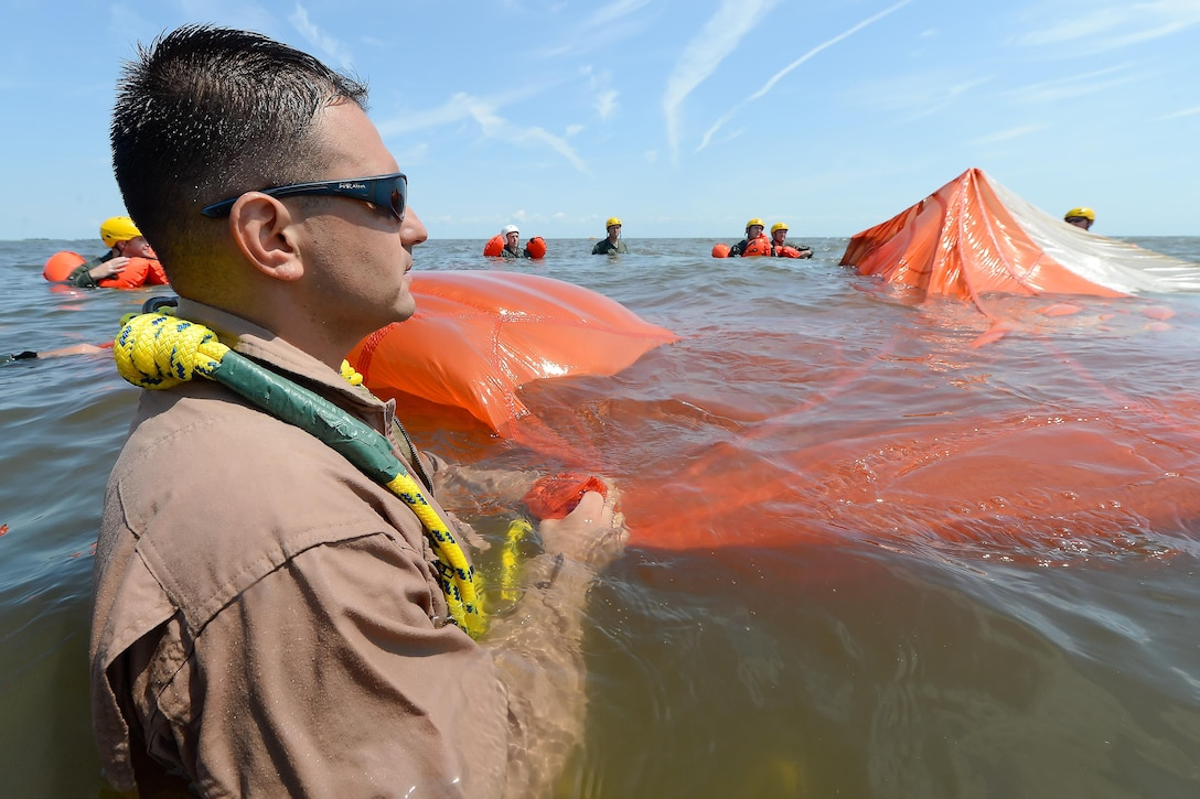 Tech. Sgt. Joseph Monreal, the 436th Operations Support Squadron Survival, Evasion, Resistance and Escape Operations flight chief, watches as a trainee uses a seam in a C-9 round parachute canopy to move from one edge to the other during aircrew water survival refresher training in the Delaware Bay July 17, 2015, near Dover Air Force Base, Del. Aircrew members of the 436th Airlift Wing and 512th Airlift Wing operate the C-5M Super Galaxy and C-17A Globemaster III, and had members who participated in the required refresher training. (U.S. Air Force photo/Greg L. Davis)