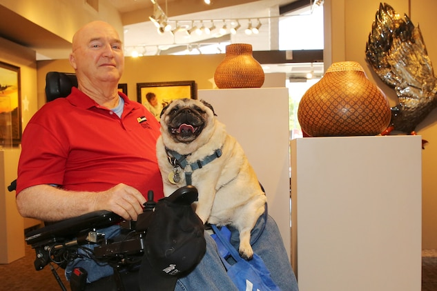 Jim Russell sits in the middle of the The Janice Griffiths Gallery with his rotund service pug, Mr. Beau, resting on his lap. The dim lights and cool interior of the gallery offer both some relief from the heat of the day as Russell recounts his tale of his life journey from military discipline to artistic expression.