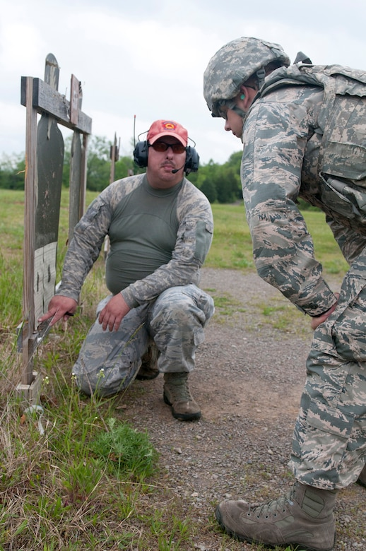 Staff Sgt. Jeremy Strange, a Combat Arms Training and Maintenance instructor with the Kentucky Air National Guard's 123rd Security Forces Squadron, gives shooter site corrections to Senior Airman Richard Lunsford, another CATM team member, during annual weapons qualifications training at Fort Knox, Kentucky, May 16, 2015. (U.S. Air National Guard photo by Staff Sgt. Vicky Spesard)