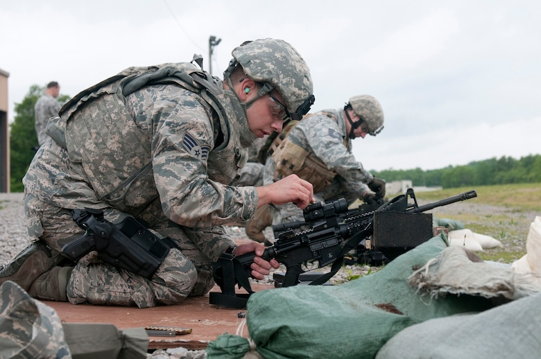 Senior Airman Richard Lunsford, a Combat Arms Training and Maintenance team member from the Kentucky Air National Guard's 123rd Security Forces Squadron, makes site adjustments on an M68 close combat optic attached to an M4 carbine during annual weapons qualifications training at Fort Knox, Kentucky, May 16, 2015. (U.S. Air National Guard photo by Staff Sgt. Vicky Spesard)