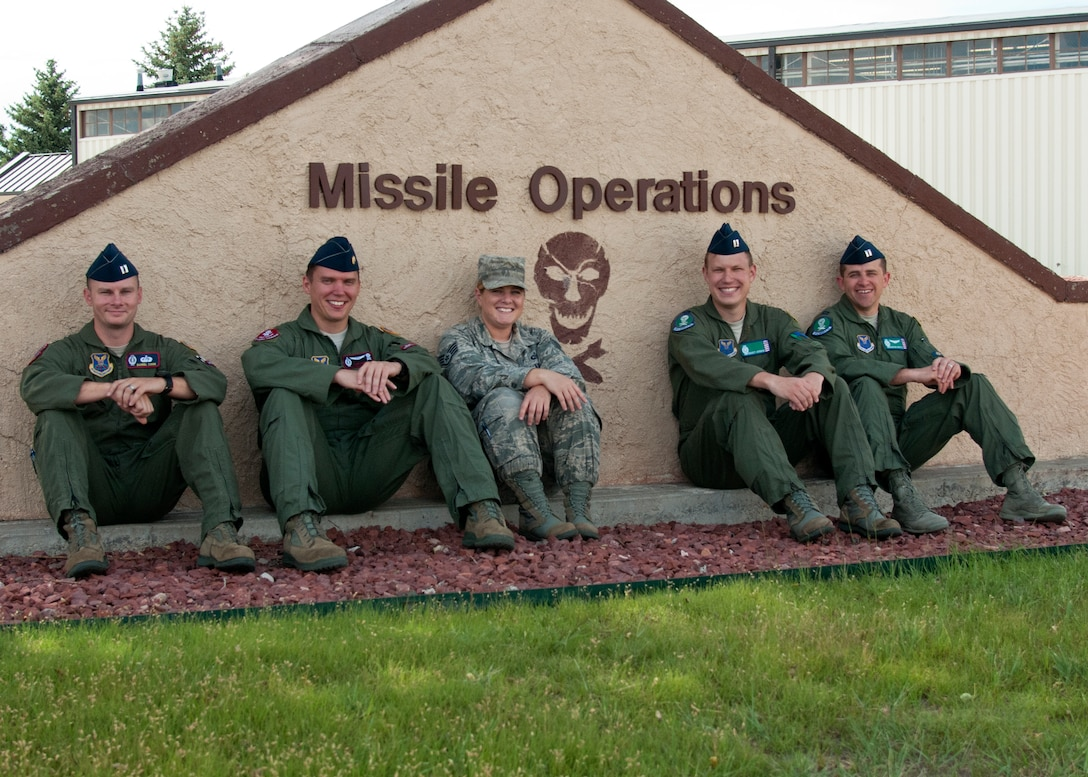 From the left, Capt. Daniel Cook, 90th Operations Support Squadron; Maj. Thomas Perry, 320th Missile Squadron; Staff Sgt. Jennifer Cornett, 321st Missile Squadron; along with Capts. Bennett Johnson and Joshua Wenta, 321st MS, sit in front of the 90th Operations Group's sign, July 15, 2015. These Airmen rescued five people in the previous month while on a TDY in Florida. (U.S. Air Force photo by Airman 1st Class Malcolm Mayfield)