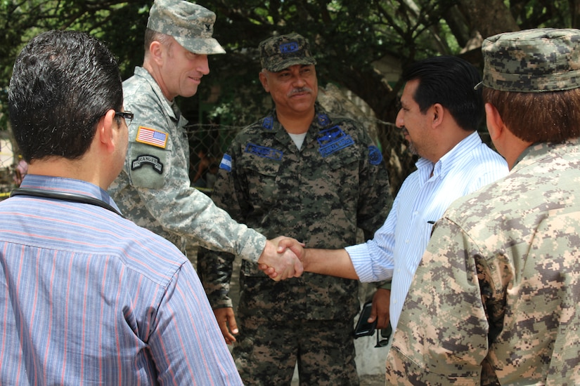 Col. Robert Harman (left), Commander of Joint Task Force-Bravo, and Lt. Col. Fredy Obando (center), Commander of Soto Cano Air Base, greet Manuel Cartagena (right), Deputy Mayor of Comayagua, as he arrives at the Medical Readiness Training Exercise site in the Ramon Ortega School located in Las Liconas, Comayagua, July 29, 2015. Medical Readiness Training Exercises are carried out in coordination with local civil authorities and ministries of health, and allow U.S. service members the opportunity to help local communities while validating their ability to provide services iin expeditionary environments.  (U.S. Army photo by Maria José Pinel)
