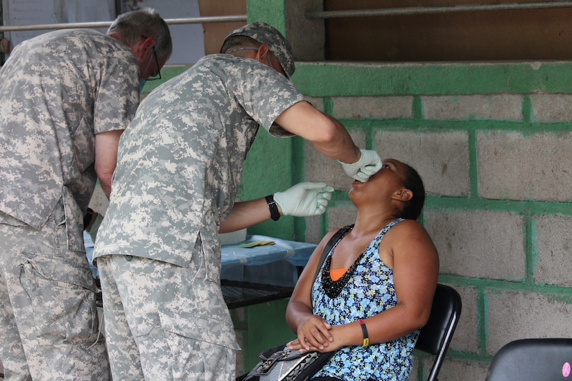 Sgt. Kyron Brown (center), assists Col. Bruce Bikson (far left), General Dentist from JTF-Bravo's Medical Element,  as they perform a dental extraction during a two -day Medical Readiness Training Exercise in the Ramon Ortega School of Las Liconas, Comayagua, July 29, 2015. During these exercises, the people from nearby communities can receive much -needed free dental care, preventive medical care, vitamins and other medication, as well as wellness checkups.  (U.S. Army photo by Maria José Pinel)