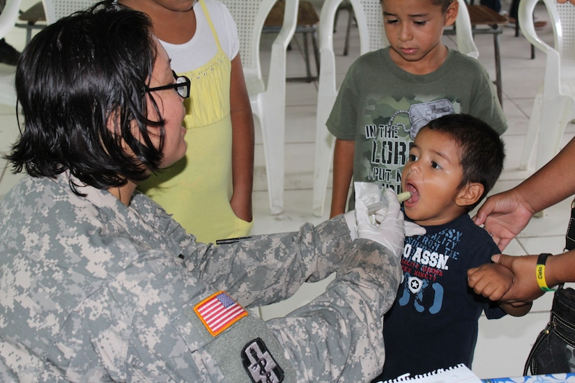 Sgt. Mary King, a preventive medicine specialist from JTF-Bravo's Medical Element, provides a four- year -old boy with antiparasitic medication during a two -day Medical Readiness Training Exercise in the village of Las Liconas, Comayagua, July 29, 2015.  These exercises allow US service members to engage with the local community and partner with the Honduran Ministry of Health, while validating their ability to provide services in the field. (U.S. Army photo by Maria José Pinel)