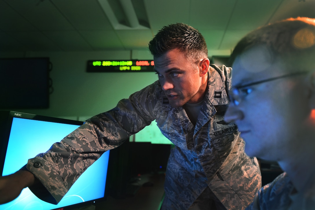 Capt. Matthew Lohmeier, 460th Operations Group Block 10 chief of training, stands in the Standardized Space Trainer July 22, 2015, on Buckley Air Force Base, Colo. The SST is a state-of-the-art training suite designed to emulate the new Block 10 operations floor environment and increase the speed and efficiency with which new space operators learn their mission. (U.S. Air Force photo by Senior Airman Darren Scott/Released)