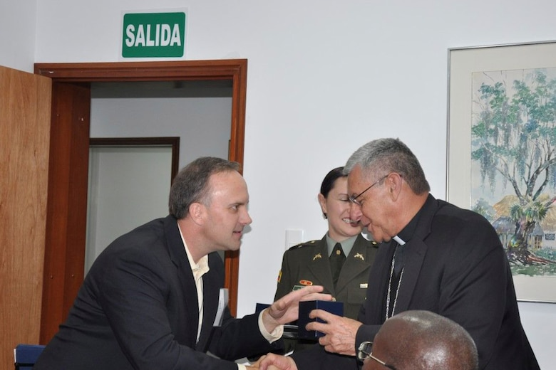 U.S. Air Force Master Sgt. Charles Williams Chaplain Assistant, receives a gift from Monsignor Fabio Suescun Mutis, Archbishop for the Colombian Military, during a  (Courtesy Photo/Released)